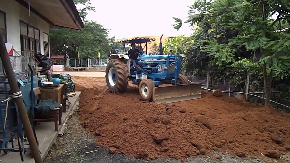 Трактор расчищает территорию перед строительством